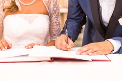 Groom during the wedding signature. Bride and Groom sign on registration of marriage during your wedding ceremony Royalty Free Stock Images