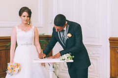 Bride and groom signing marriage license Royalty Free Stock Image