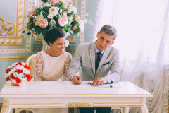 Bride and groom signing marriage license Royalty Free Stock Photo