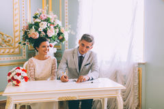Bride and groom signing marriage license Stock Photo