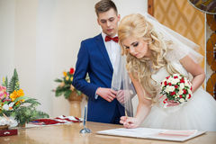 Bride and groom signing marriage wedding certificate. At registry Royalty Free Stock Images