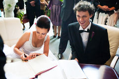 Bride and groom signing registry Royalty Free Stock Images