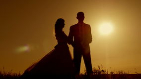 Bride and groom silhouette kissing in beautiful orange-red sunset sky stock video