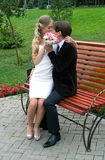 Bride and groom sit on the bench Royalty Free Stock Photo