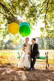 The bride and groom sit on the bench with balloons Royalty Free Stock Photos