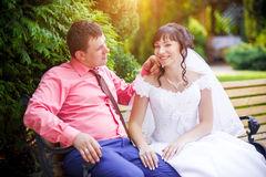 Bride and groom sit on the bench Royalty Free Stock Photography
