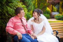 Bride and groom sit on the bench Stock Photo
