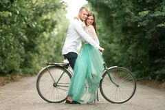 Bride and groom sit on bicycle on forest road, embrace and laugh Stock Photo