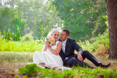 Bride and groom sit on grass in the park Royalty Free Stock Photography