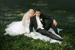 Bride and  groom sit on a green grass Royalty Free Stock Photos