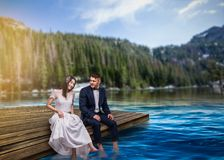 Bride and groom sit on the pier, romantic scene. Bride and groom sit on the pier and wet their feet in the water, romantic scene on the lake, mountains and stock photo