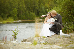 Bride and groom sit on riverbank Royalty Free Stock Photo