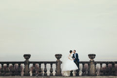Bride and groom sit on the stone balcony with a deep colored sky stock images