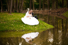 Bride and groom sitting on bank on lake Royalty Free Stock Photos