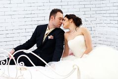 Bride and groom sitting on bed in bedroom Royalty Free Stock Photo