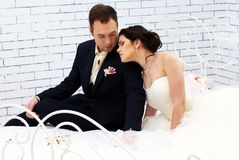 Bride and groom sitting on bed in bedroom Royalty Free Stock Image