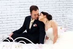 Bride and groom sitting on bed in bedroom Stock Photos