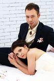 Bride and groom sitting on bed in bedroom Royalty Free Stock Images