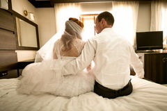 Bride and groom sitting on bed and hugging Stock Images