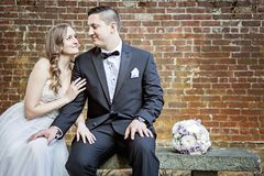 Bride and Groom sitting on bench in front of brick wall. A bride and groom sitting on a bench in front of a brick wall in a garden Royalty Free Stock Images