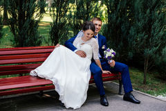The bride and groom sitting on bench. The groom hugs the bride. The bride and groom sit on a bench. The groom hugs the bride Stock Photos