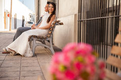 Bride and groom sitting on a bench Stock Image