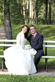 Bride and groom sitting on bench in park Stock Photography