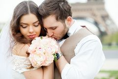 Bride and groom sitting on bench in park, holding hands of each other and bouquet. Groom holding his head on bride`s shoulder and. Bride smiling broadly stock photo