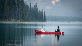 Bride and groom sitting on the boat along the Emerald Lake is located in Yoho National Park, British Columbia, Canada stock photo