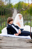 Bride groom sitting on the bridge Royalty Free Stock Images