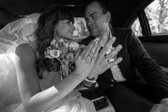 Bride and groom sitting in car and showing engagement rings Royalty Free Stock Image