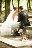 Bride and groom sitting face to face on bench Stock Image