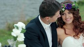 The Bride and Groom are Sitting on a Green Field. Meadow and enjoy each other.Picnic newlyweds on green field meadow.Loving wedding couple outdoor. Bride and stock video footage
