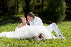 Bride and groom sitting at green grass Royalty Free Stock Image