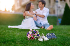 Bride and groom are sitting on the green grass in the park Royalty Free Stock Image