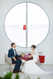 Bride and groom sitting in indoors cafe Stock Photo
