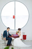 Bride and groom sitting in indoors cafe Royalty Free Stock Photos