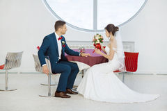 Bride and groom sitting in indoors cafe Stock Photos