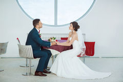 Bride and groom sitting in indoors cafe Stock Images