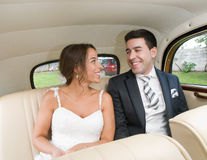 The bride and groom are sitting inside a retro car and smiling. Royalty Free Stock Images