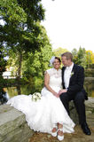 Bride and groom sitting at a lake in autumn Royalty Free Stock Photography