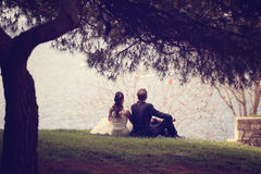 Bride and groom sitting at lake Royalty Free Stock Images