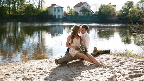Bride and groom sitting on the log. On the sand near the river. Posing to photographer and enjoying each other. Beautiful backlight stock video footage
