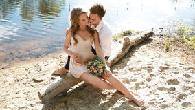 Bride and groom sitting on the log stock video