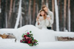 Bride and groom are sitting on the log in the winter forest. Close-up. Winter wedding. Soft focus on the bouquet Stock Photo
