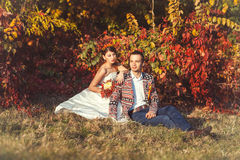 Bride and groom sitting near the autumn bush. Beautiful bride in a wedding dress and groom sitting near the bushes in the autumn forest Royalty Free Stock Photography