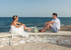 Bride and Groom sitting near the Beach Stock Photo