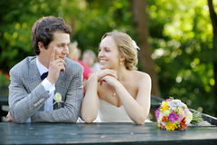 Bride and groom sitting at an outdoor cafe Royalty Free Stock Photography
