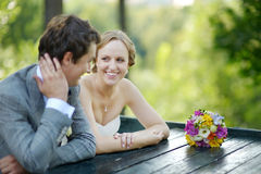 Bride and groom sitting at an outdoor cafe Royalty Free Stock Photos