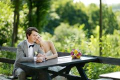 Bride and groom sitting at an outdoor cafe Stock Images